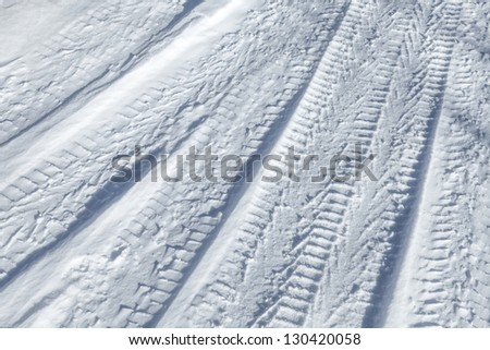 Background texture of  tire tracks on road covered with snow - stock photo