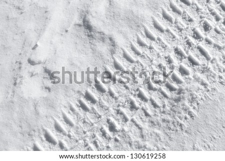 Background texture with  tire tracks on road covered with snow - stock photo