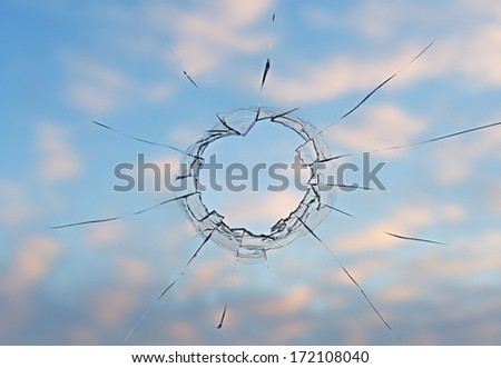 Background the broken windowpane view from  room on  blue sky with clouds. - stock photo