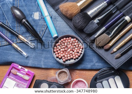 background various women's beauty accessories lie on denim