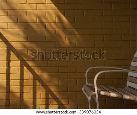 background wall texture with shadows and chair - stock photo
