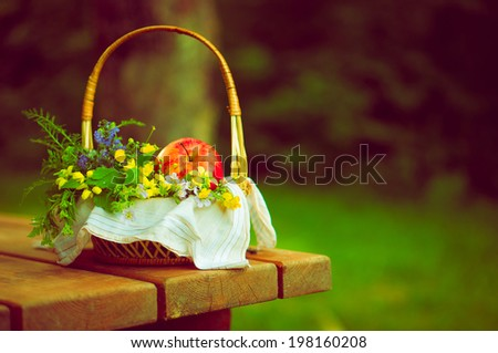 Background wicker basket with apples and flowers on wooden table - stock photo