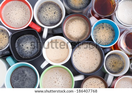 Background with a view from above of closely packed assorted mugs full of fresh hot coffee covered in froth - stock photo