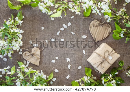 Background with apple blossoms, gift box and cardboard hearts. Place for text. Top view. - stock photo