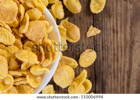 Background with cornflakes in bowl on old wooden table, space for text