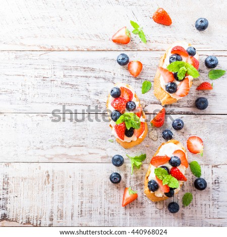 Background with crostini with grilled baguette, cream cheese, blueberry, strawberry, honey and mint on old white wooden background. Delicious appetizer or dessert. Copy space. - stock photo