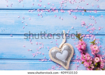 Background  with elegant  pink flowers and decorative heart on blue wooden planks. Selective focus. Place for text. - stock photo