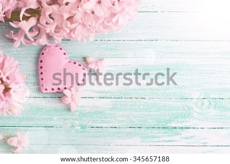 Background  with fresh flowers hyacinths  and decorative pink  heart in ray of light  on turquoise painted wooden planks. Selective focus is on heart. Place for text. - stock photo