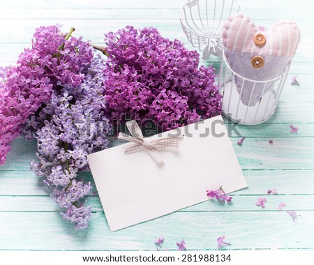 Background  with fresh lilac flowers,  textile decorative heart  and empty tag on turquoise painted wooden planks. Selective focus. Place for text. Toned image.  - stock photo