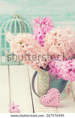 Background with fresh pink hyacinths in vase, little pink heart  on white wooden planks against turquoise wall. Selective focus.  Toned image. - stock photo