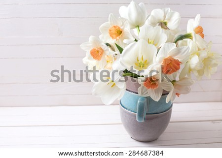 Background with fresh spring  pink daffodils  and white tulips flowers in vase  on white wooden planks. Selective focus. Place for text. - stock photo