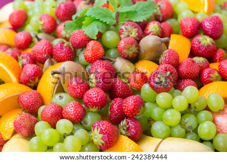 Background with fresh strawberries, grapes, bananas and oranges - stock photo
