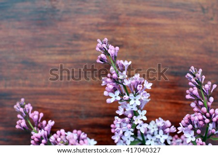 Background with fresh violet lilac flowers on brown painted wooden background. Selective focus. Place for text. Rectangle image