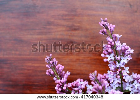 Background with fresh violet lilac flowers on brown painted wooden background. Selective focus. Place for text. Rectangle image - stock photo