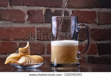 background with glass of Fresh Beer and plate full of chips