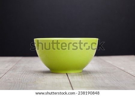 Background with green bowl on wooden table over black wall - stock photo