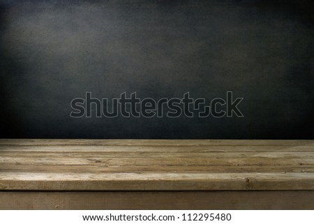 Background with grunge black wall and wooden table deck. - stock photo