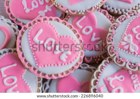 """background with homemade cookies with frosting in the shape of hearts and the words """"love"""" - stock photo"""