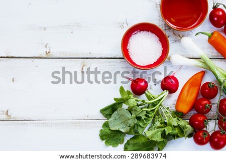 Background with Ingredients of Fresh vegetable salad on white wooden board. Healthy or vegetarian eating concept.