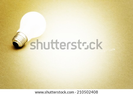 Background with lit lightbulb. Isolated on yellow - stock photo