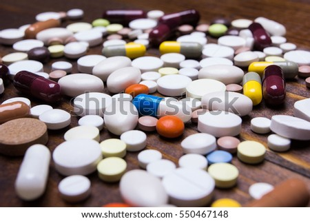 Background with medicines, pills, supplements and vitamins tablets on wooden background