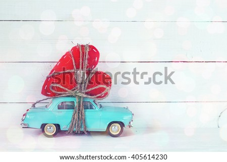 Background with miniature blue toy car carrying a heart on white painted planks. Place for text. - stock photo