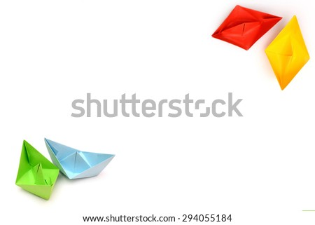 background with origami paper boats, four ships, boats in the corner, red yellow blue green boat origami boats in focus, several ships