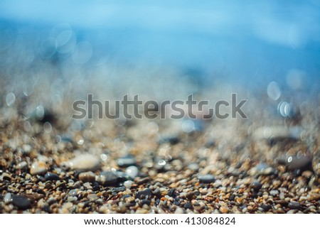 Background with pebbles and blue sea with extremely shallow depth of field and swirly bokeh - stock photo