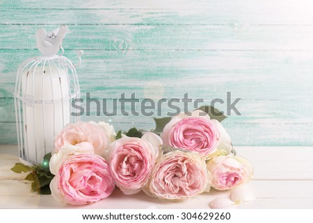 Background with  pink roses flowers and candle  in decorative bird cage in ray of light on white painted wooden background against turquoise wall. Selective focus.  Place for text. - stock photo