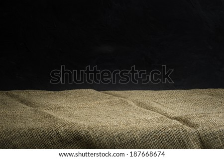 Background with sack cloth on wooden deck table and dark grunge background - stock photo