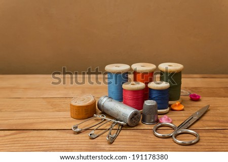 Background with sewing tools and colored thread. Sewing kit. Scissors, bobbins with thread and needles on wooden table - stock photo