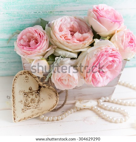 Background with sweet pink roses flowers wooden box and decorative heart on white painted wooden background against turquoise wall. Selective focus. Square image. - stock photo