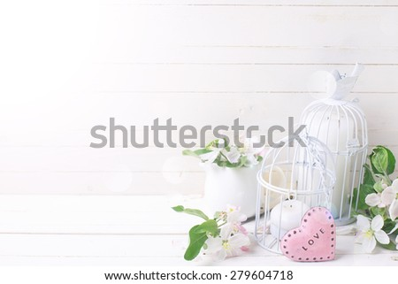 Background  with tender apple blossom, candles in decorative bird cages and little pink heart  in ray of light on white painted wooden planks. Selective focus.  - stock photo