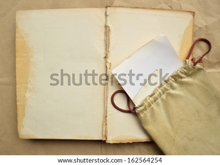 Background with vintage leather bag, with paper and empty open book