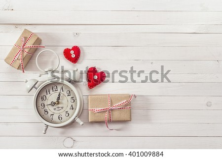 Background with white alarm clock, gift boxes and red hearts on white painted wooden planks. Place for text. Top view with copy space - stock photo