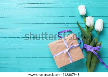 Background with white tulip flowers and gift box  on turquoise wooden background. Selective focus. Place for text. - stock photo