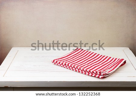Background with white wooden table and red striped tablecloth - stock photo
