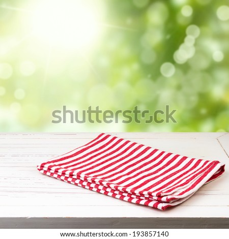 Background with white wooden table and red striped tablecloth over green bokeh - stock photo