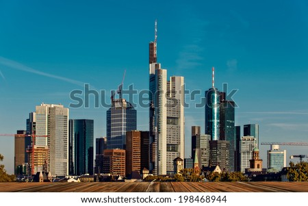 background with wooden deck table and Skyline in Frankfurt - stock photo