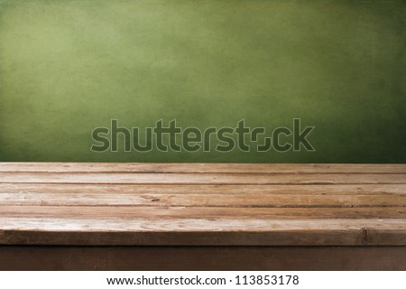Background with wooden deck tabletop and grunge green wall - stock photo