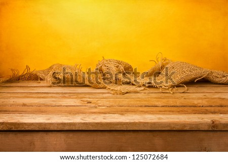 Background with wooden table and sackcloth over grunge yellow background - stock photo