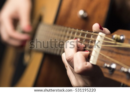 background Young woman clamped with fingers guitar strings and plays a melody
