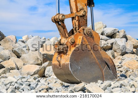 Backhoe bucket with a large pile of rocks in the background against a blue sky. - stock photo