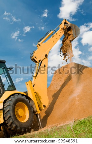 Backhoe loader excavator equipment at sand construction works - stock photo