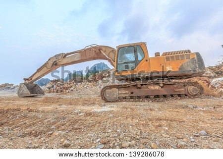 backhoe resting bucket and arm at lime industry site with mountain background - stock photo