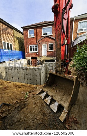 Backhoe scoop at residential home renovation construction site - stock photo