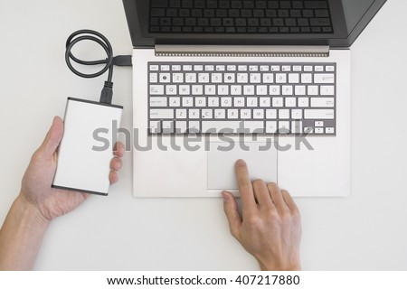 Backing up computer files to external portable hard drive - stock photo