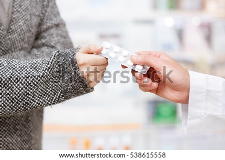 Backing up her health. Cropped closeup of a pharmacist passing pills blister to his customer at the drugstore