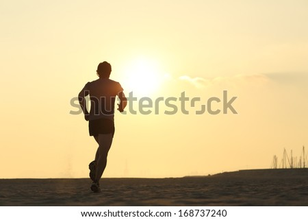 Backlight of a jogger running on the beach with the sun beside - stock photo