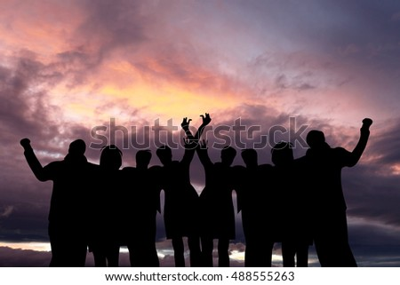 Backlight shot of Multi-racial group of people with raised arms looking at sunset.  Success, friendship, community and  happiness concepts.